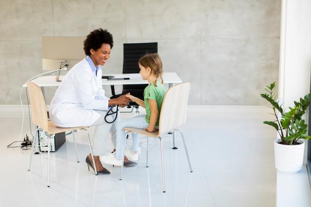 아프리카 계 미국인 여성 의사의 소아과 의사 시험에서 귀여운 소녀