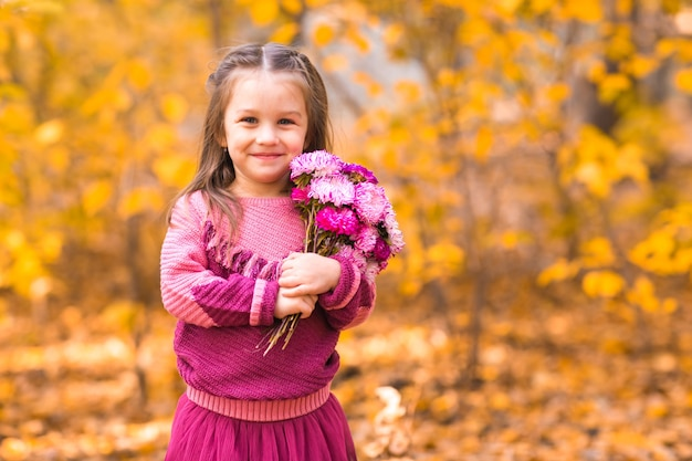 Cute little girl in autumn park with pink flower bouquet.