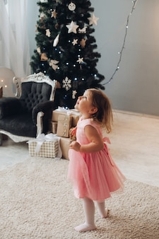 A cute little girl in a beautfiul dress have a lot of fun near the christmas tree at home