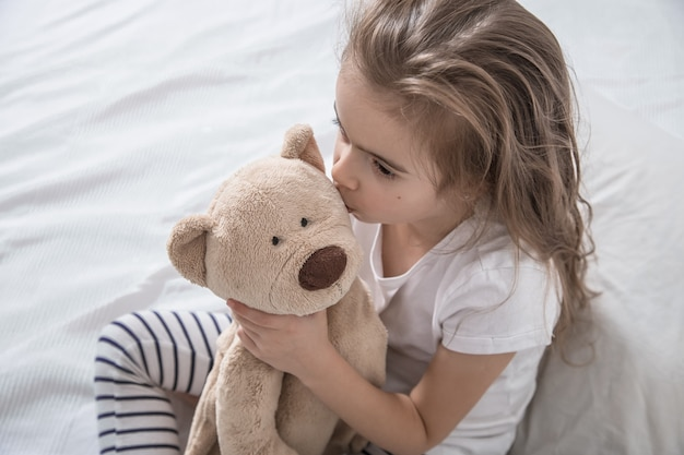 Cute little girl in bed with soft toy