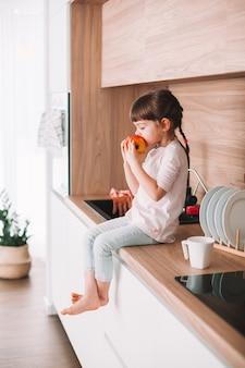 부엌 표면에 앉아 육즙 빨간 사과 물고 귀여운 소녀. 건강한 먹는 개념.