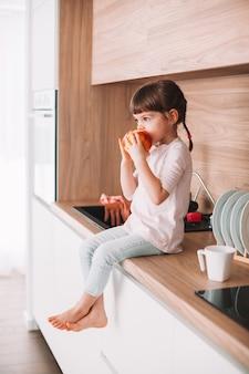 부엌 표면에 앉아 빨간 사과 물고 귀여운 소녀. 건강한 먹는 개념.