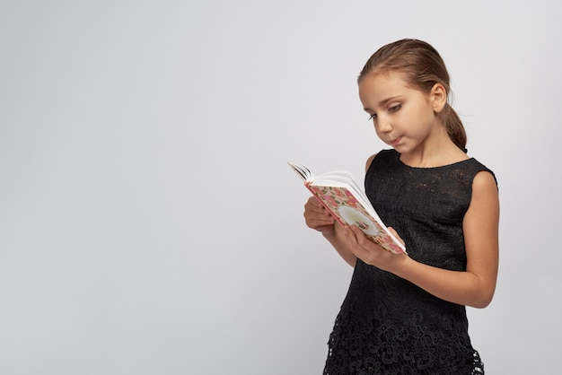 Cute little girl in a black dress with passionate pensive expression reading a book. large studio portrait isolated white background