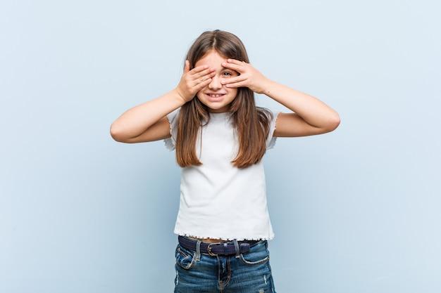 Милая маленькая девочка мигает сквозь пальцы испуганно и нервно