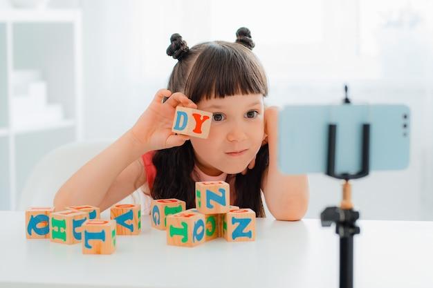 Милая маленькая девочка-блогер играет с деревянными разноцветными кубиками с буквами и показывает их онлайн