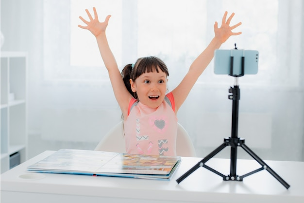 Cute little girl blogger smiles at the camera and shows cool thumbs up records videos on a smartphone camera on a tripod for her followers her followers on the internet