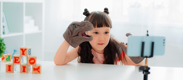 Cute little girl blogger smiles at the camera and shows dinosaur skeleton records plays a performance videos on a smartphone camera on a tripod for her followers her internet
