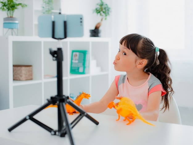 Cute little girl blogger smiles at the camera and shows dinosaur skeleton records videos on a smartphone camera on a tripod for her followers her followers on the internet