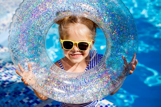Cute little girl blonde in sunglasses laughs in the pool holding a lifeline