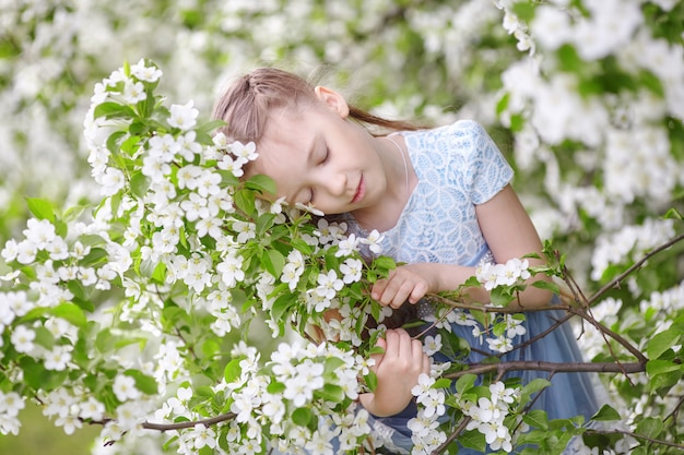 Cute little girl in blooming apple tree garden at spring