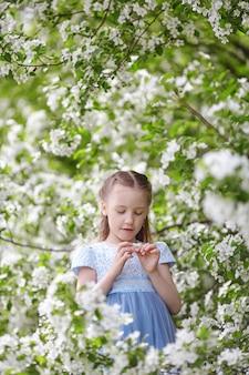 Cute little girl in blooming apple tree garden