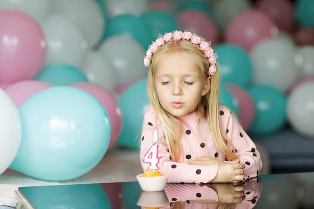 Милая маленькая девочка выдува свечи на день рождения