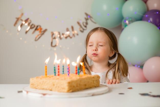 귀여운 소녀 풍선을 배경으로 집에서 생일 케이크에 촛불을 불어. 자녀의 생일