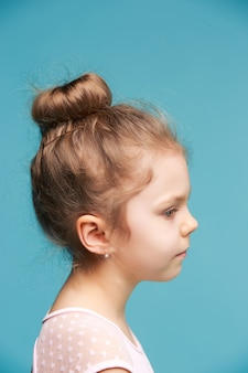 Cute little girl on a blue background close-up