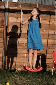 Cute little girl in blue dress playing on playground outdoors she swinging