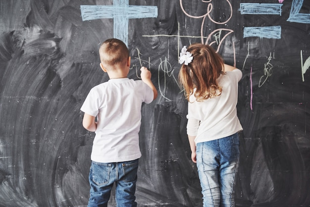 Cute little girl and boy drawing with crayon color on the wall. work of child. cute pupil writing on chalkboard