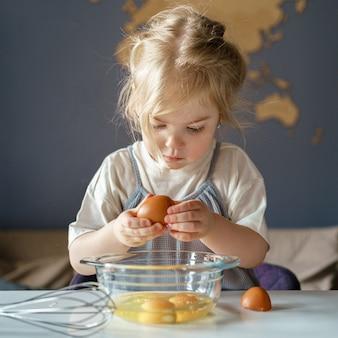Милая маленькая девочка разбивает яйца в миску во время готовки с мамой