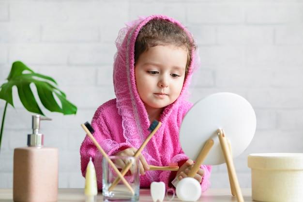 Милая маленькая девочка, чистящая зубы, мытье лица в ванной комнате, глядя в зеркало. ежедневная забота о ребенке.