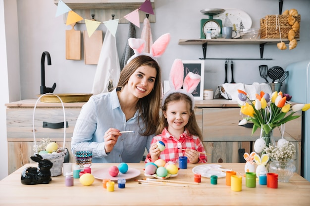 Cute little girl in bunny ears painting eggs for easter with mother