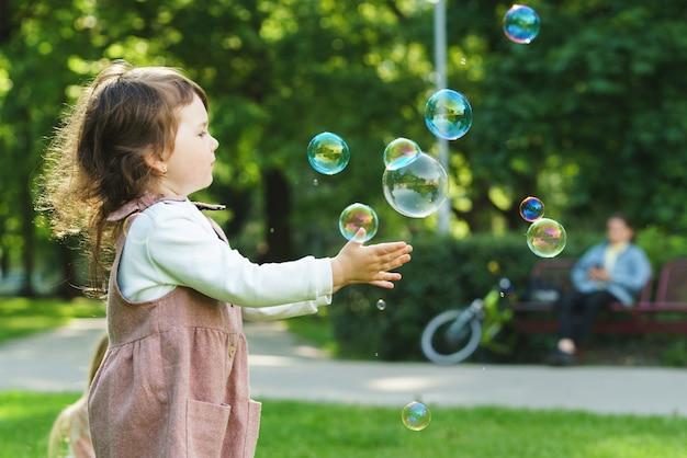 Милая маленькая девочка ловит мыльные пузыри в городском парке