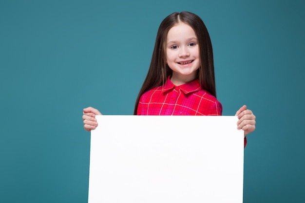 Cute little girl in checkered shirt with brunet hair hold clear blank placard