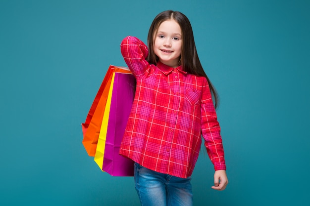 Cute little girl in checkered shirt with brunet hair hold different bags