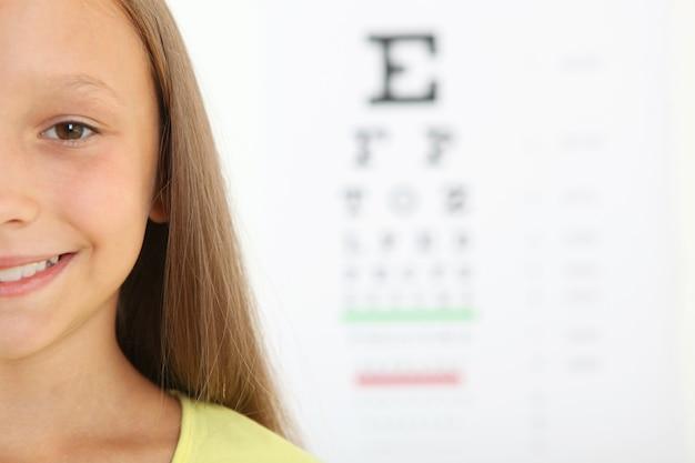 Милая маленькая девочка проверяет зрение с помощью проверки зрения офтальмолога