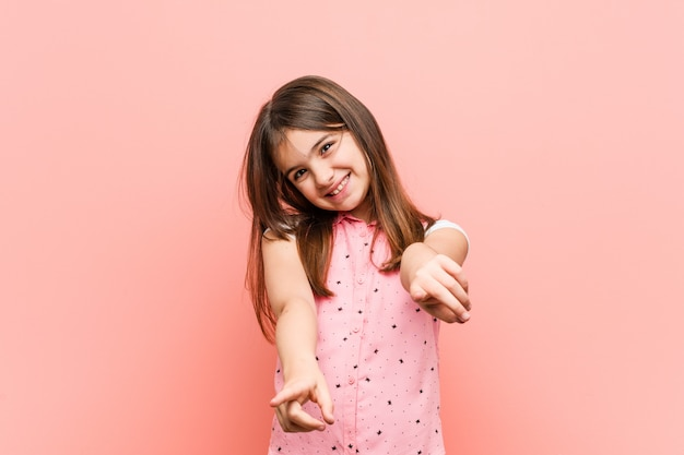 Cute little girl cheerful smiles pointing to front.