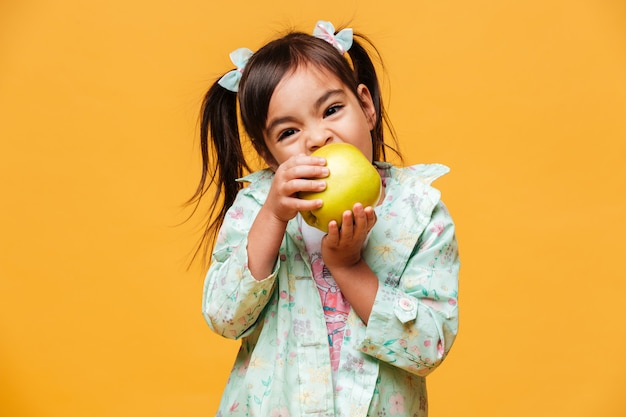 Cute little girl child eating apple.