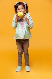 Милая маленькая девочка ребенок ест яблоко.