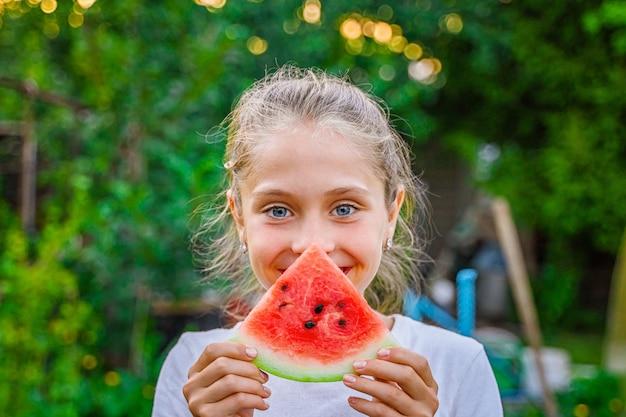 Cute little girl child eating watermelon in the green garden