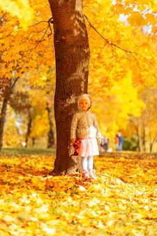 Cute little girl child in fashionable clothes with a toy stands near a tree with fall yellow foliage on a sunny autumn day.