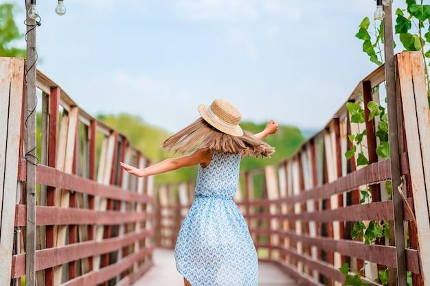 Милая маленькая девочка в шляпе и платье на берегу сказочного озера