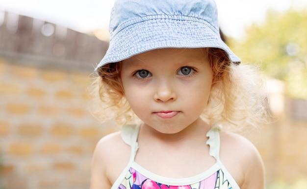 Милый портрет ребенка маленькой девочки в голубой панаме джинсовой ткани на лете. фигуристая блондинка кавказская грустная