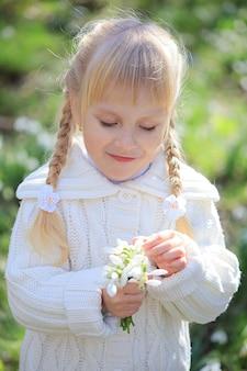 Snowdrops의 신선한 꽃다발을 고려하는 귀여운 소녀. 봄 시간. 화이트에 어린 소녀는 숲에서 산책
