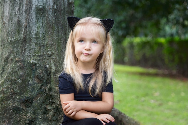 Cute little girl in costume of black cat for halloween