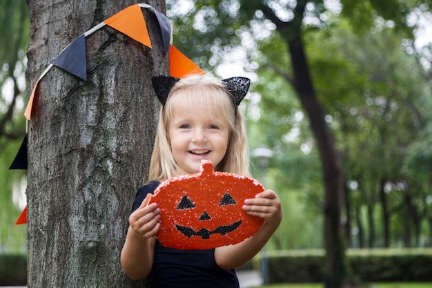 Cute little girl in costume of black cat for halloween