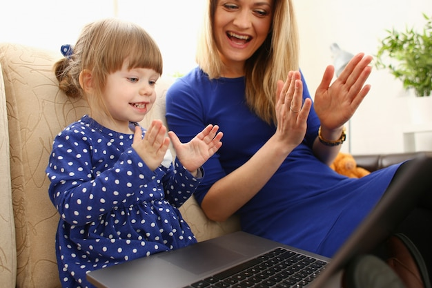 Cute little girl on couch with mom use laptop
