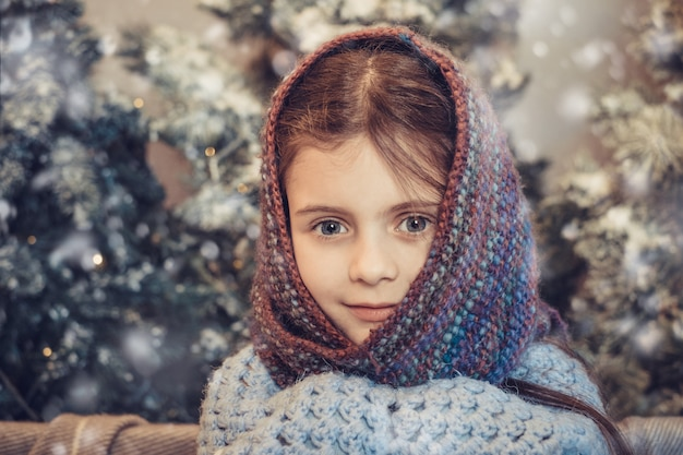 Cute little girl covered in warm scarf waiting for christmas