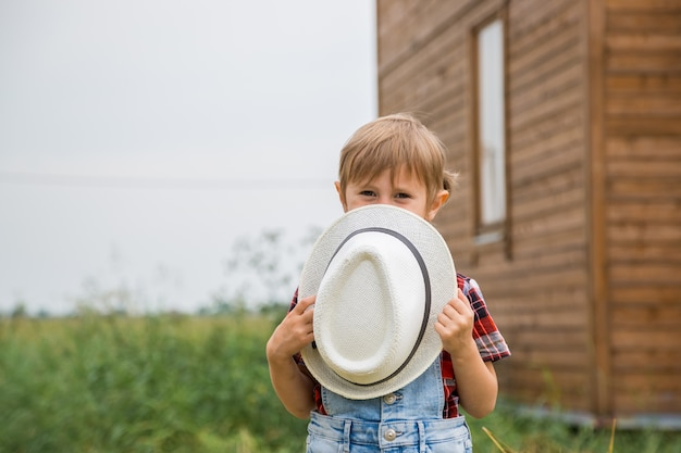 Cute little girl in a cowboy hat dressed in a denim shorts spends time in a village