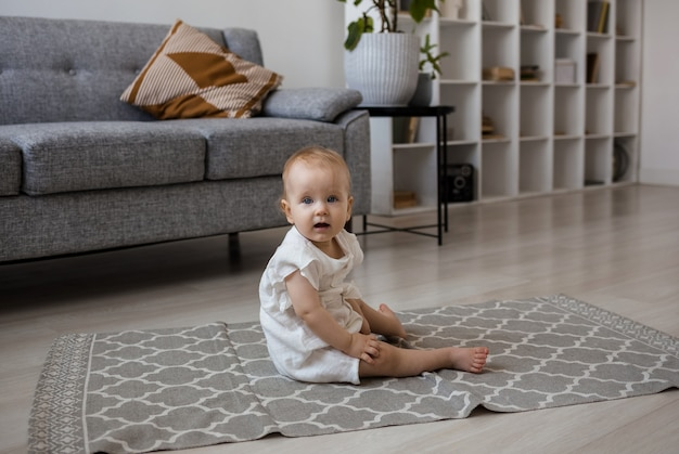 A cute little girl in a crimson jumpsuit is sitting on a gray carpet in the room