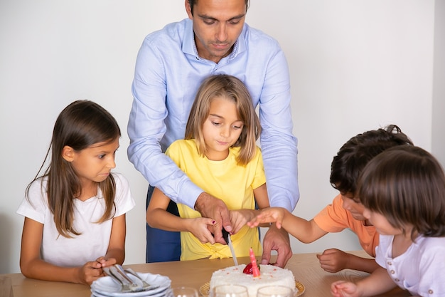 Cute little girl cutting birthday cake with help of father. happy adorable children celebrating birthday together and waiting for dessert at dining room. childhood, celebration and holiday concept