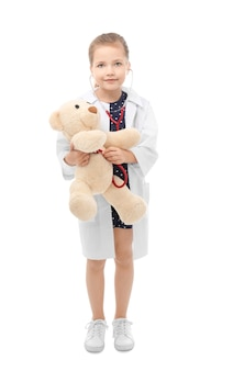Cute little girl in doctor uniform playing with toy bear on white