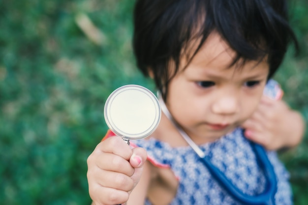 의료 헤드폰으로 귀여운 작은 소녀 의사