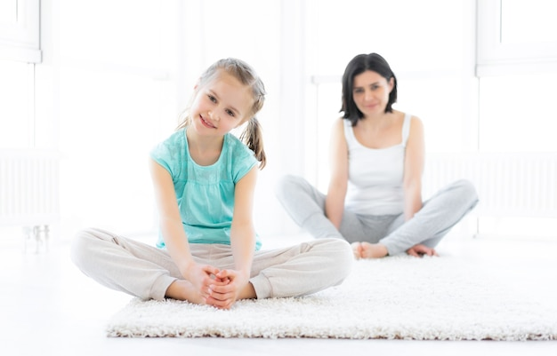 Cute little girl doing sports with mother in light room
