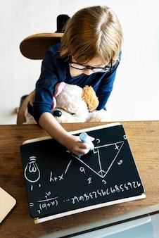 Cute little girl drawing on a blackboard