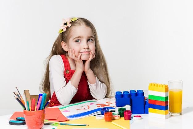 Милый рисунок маленькой девочки с краской и кистью дома