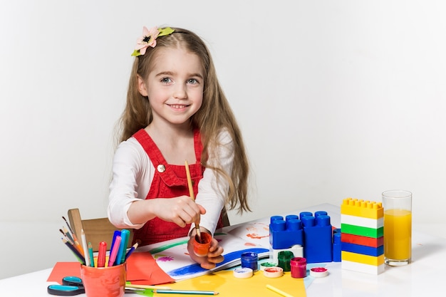 Bambina sveglia che disegna con vernice e pennello a casa