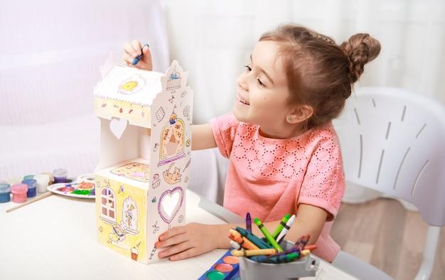 Милая маленькая девочка, рисование карандашами дома
