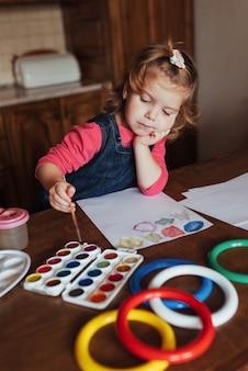 Милая маленькая девочка рисует круг из разноцветных красок